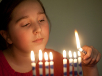 A girl lighting Chanukah candles