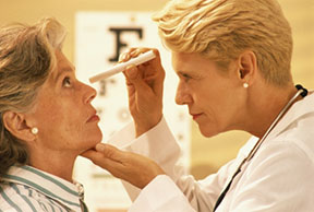 A woman getting an eye check up by a doctor