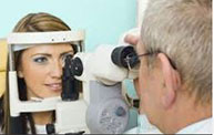 Eye doctor giving woman a check up